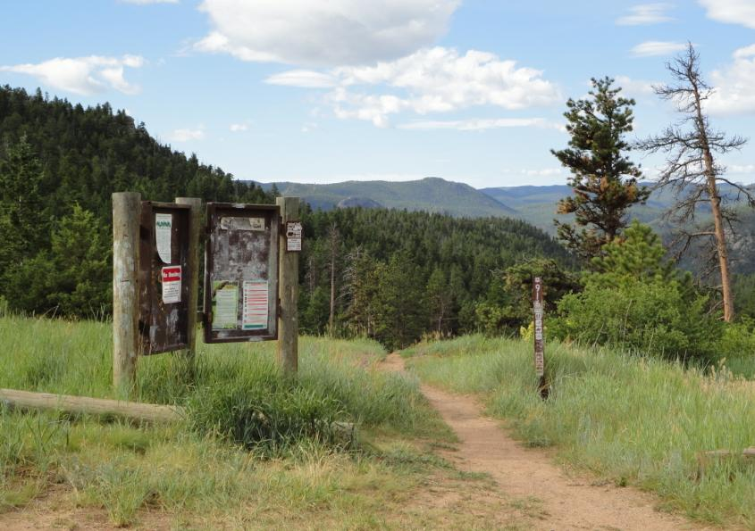 Image of the Coulson Gulch informational kiosk and trail with a meadow in the background