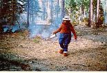 Smokey Bear works on a perscribed fire using a drip torch to light a controlled fire.