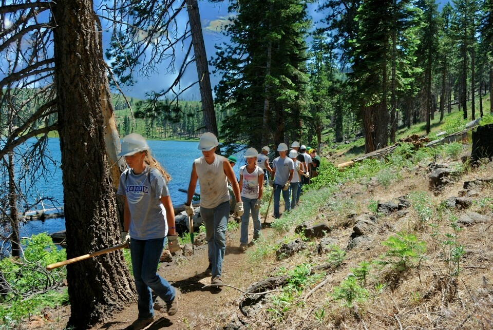 Volunteers carry tools while hiking to their work site.