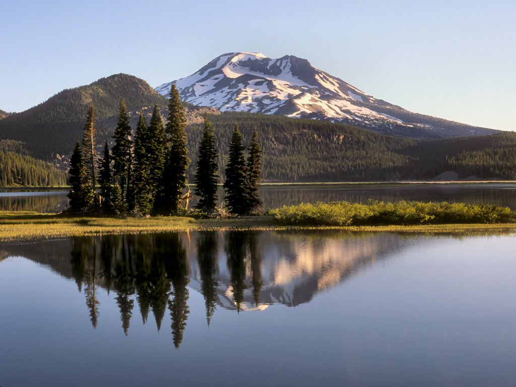 Photograph:  Snow capped mountain reflecting off of a glassy lake.