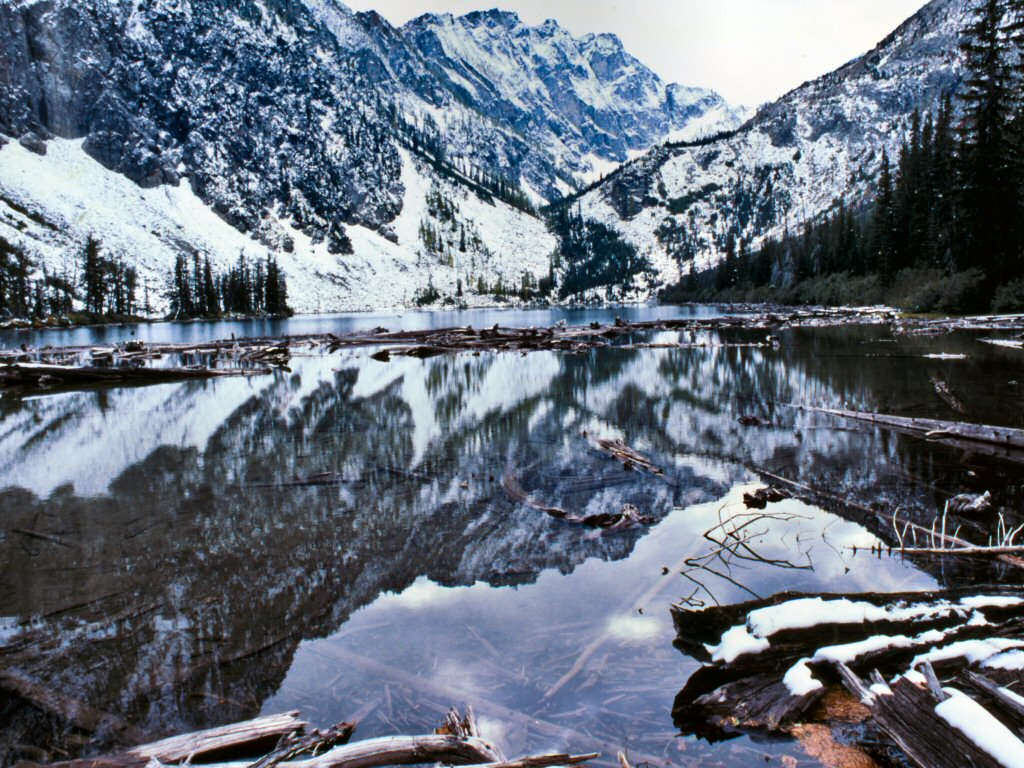 Photograph: Clear lake with reflection of surrounding snow-covered mountains.