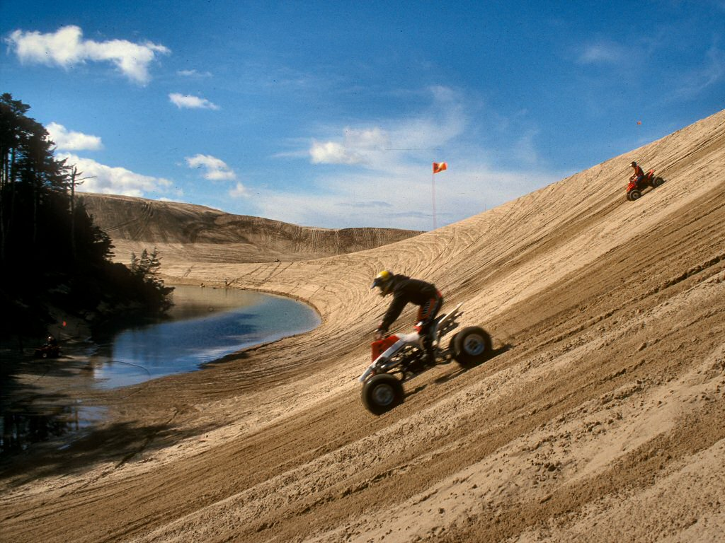 Photograph: Two people on off-highway vehicles ride down a dune.