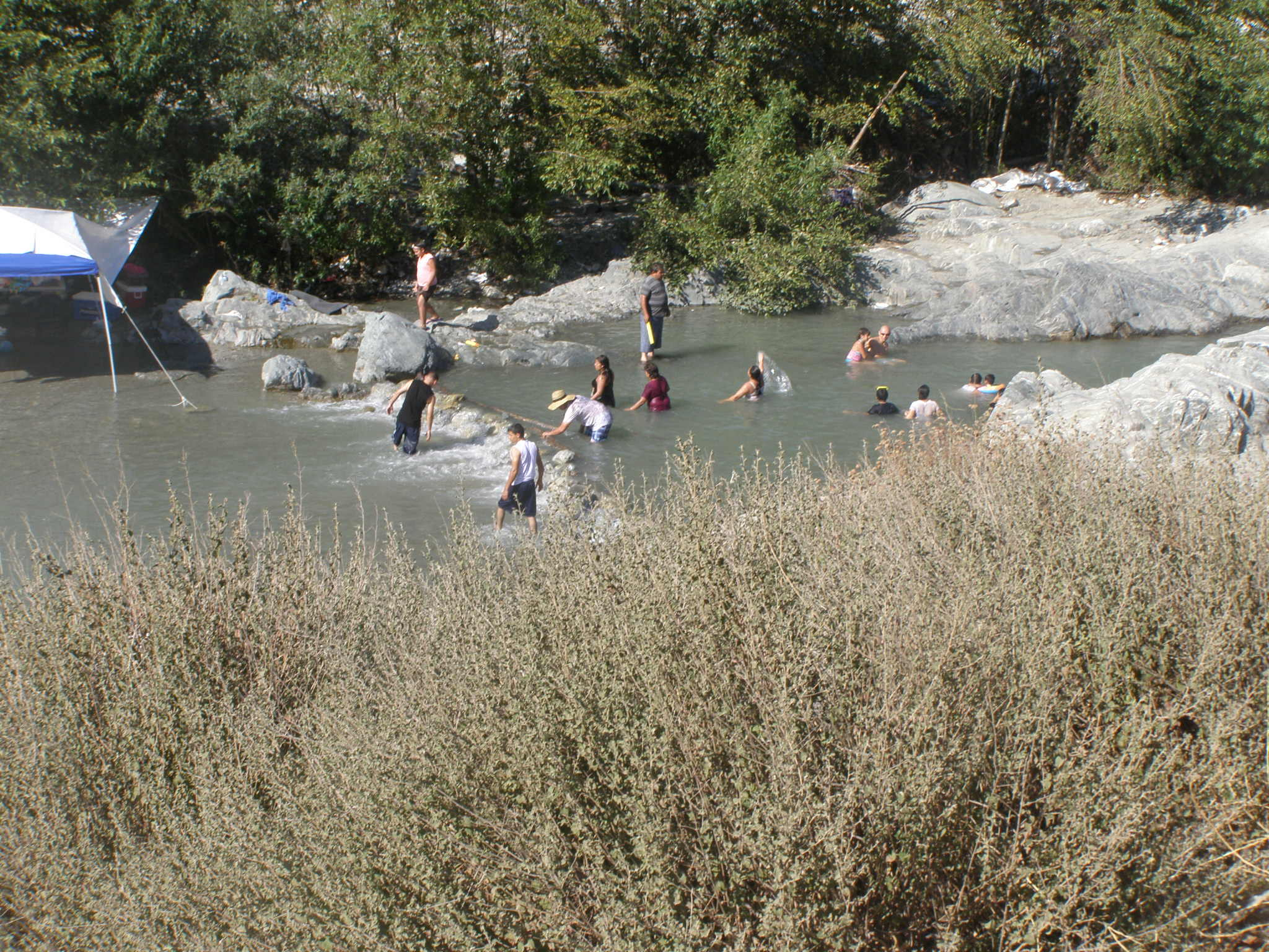 About a dozen family members wade and frolic in the San Gabriel River East Fork.