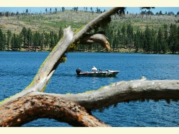 A small fishing boat is framed by a dead log in the water at Blue Lake.