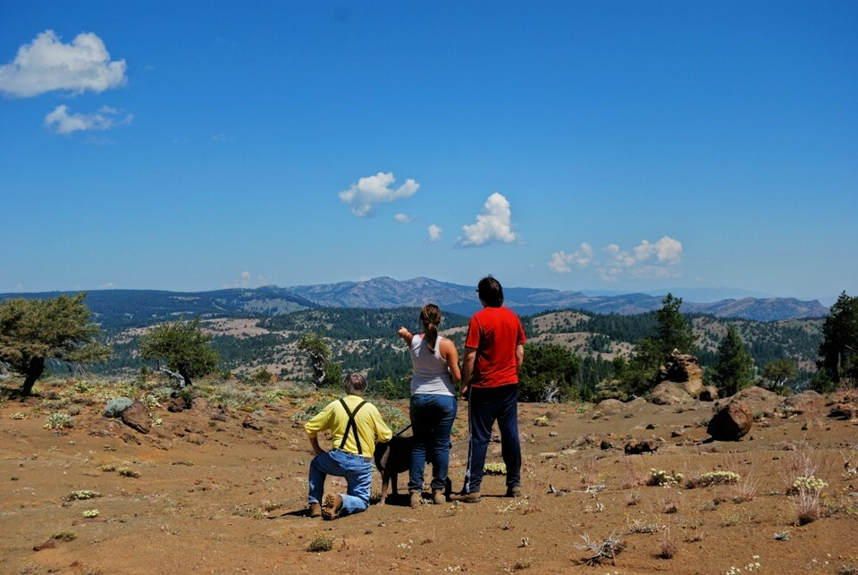 Three hikers and their dog enjoy the view from the Summit Trail.
