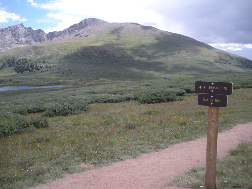 Two signs diplay at the head of the trailhead to Mount Bierstadt. The mountain is in the background.