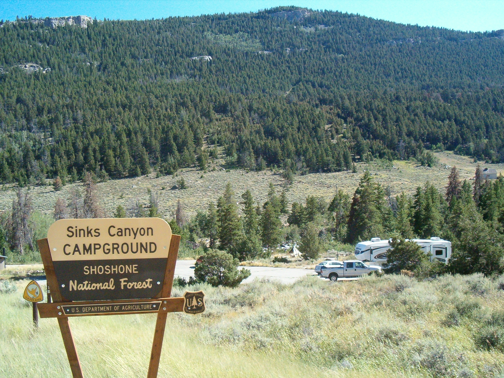 Photo showing the Sinks Canyon Campground sign, with the campground in the background