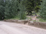 Photo of site #2 at Cold Springs Campground. Picnic table and fire grate are located above the site.