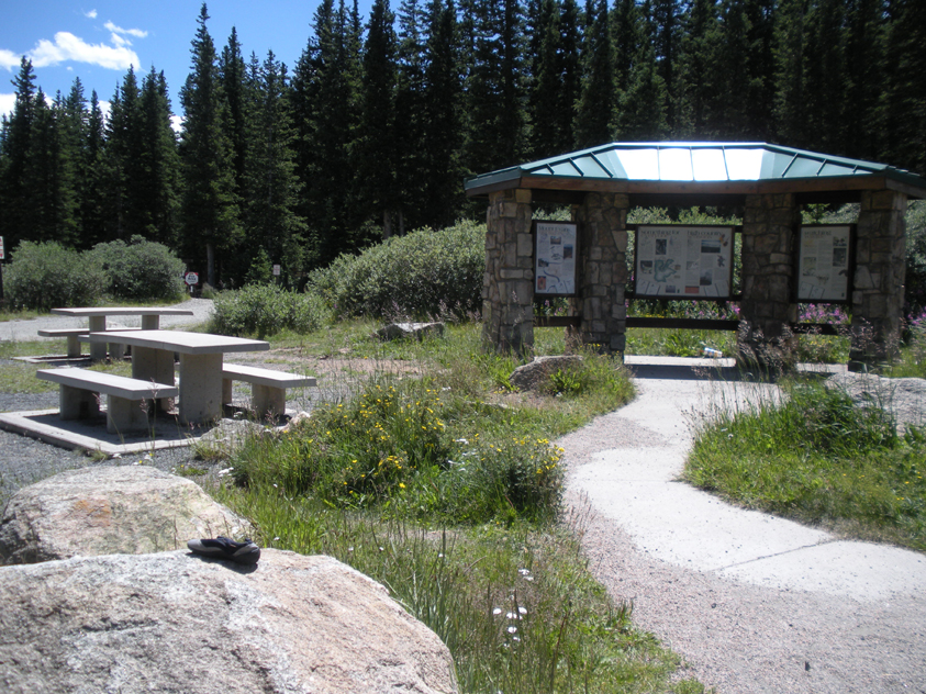 An interpretive sign posted at the entrance to the campground, with picnic tables and benches.