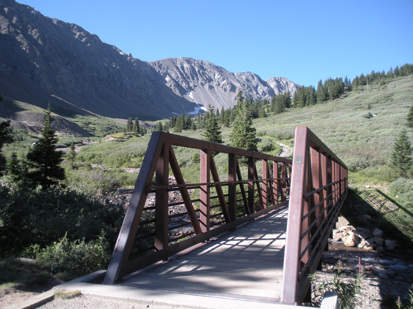 A bridge above Stevens Gulch, connecting hikers to the peaks. Grays Peak is in the background.