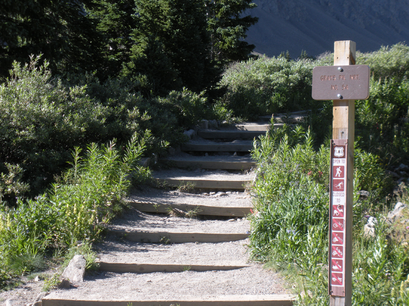 A trail sign, Grays Pk. NTR. No 54, displays at the trailhead to Grays Peak with built-in steps.