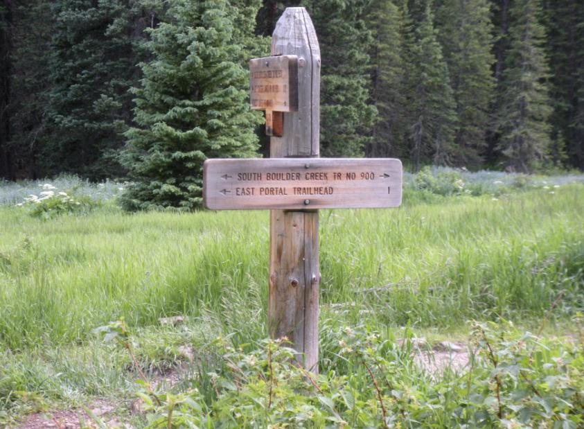 Image of the South Boulder Creek trail with a wooden sign in a grassy mountain meadow