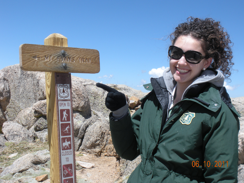Forest ranger Thalia Haro points to the trail sign to Mount Evans Trail.