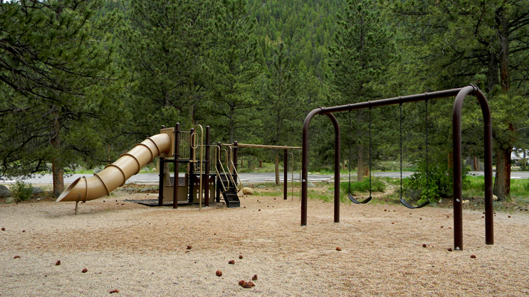 A playground area, including a slide, two swings, a monkey, and a set of steps.