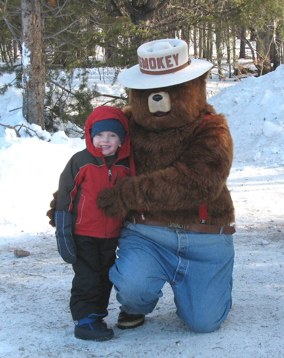Small boy in a red coat poses with Smokey Bear in the snow.