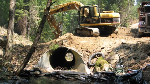 Shows heavy equipment installing a new culvert pipe