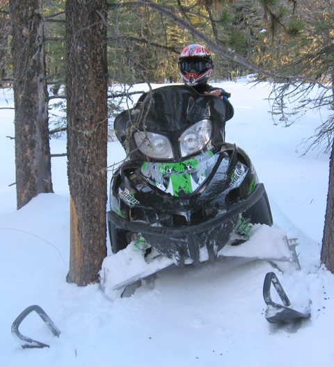 Snowmobiler Riding Through Trees