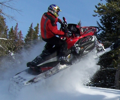 Snowmobile Jumping over Snowbank
