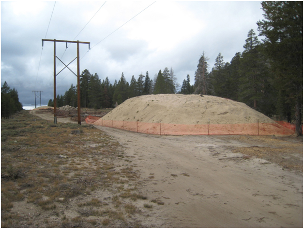 Color photo soil pile surrounded by orange fencing on right, power lines, conifer trees background.