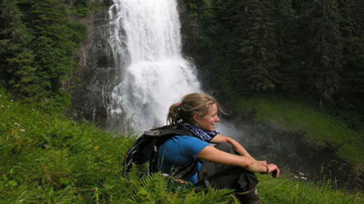 A young woman sits in a grassy area with a waterfall in the background.