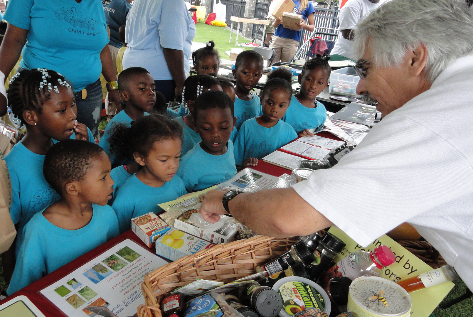 A man points out packaged foods spread out at a booth to a group of children.