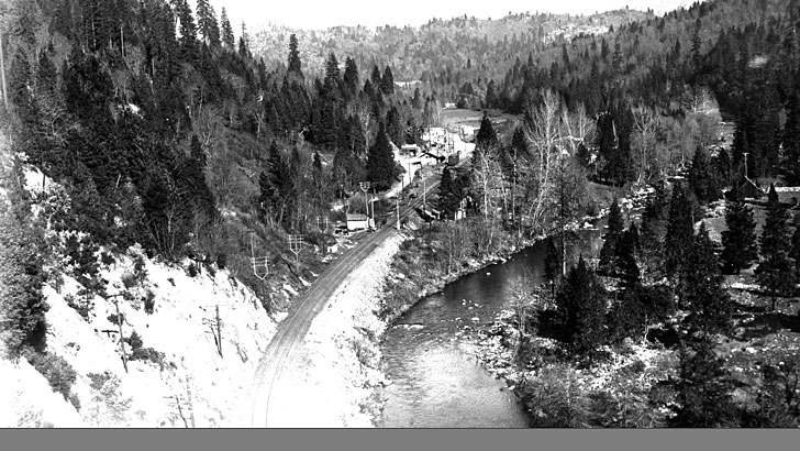 Looking down toward a town and railroad tracks next to a river in a forested environment in 1940
