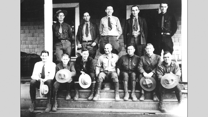 A group photo of 12 men posing in front of a building in the 1920s