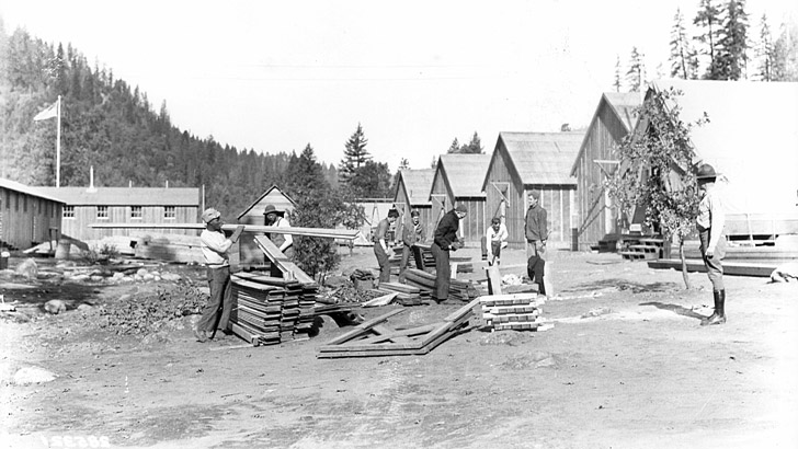 Several men work with lumber in a CCC camp of several buildings in 1934. A supervisor watches them