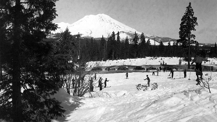 Several people are skiing in 1937. Mt. Shasta is in the background