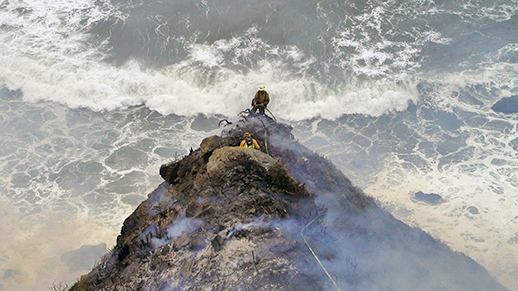 Two firefighters climb a rocky cliff above rough waters at Big Sur.
