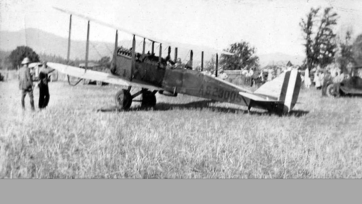 1920s. Shows a former military bi-plane parked in a field. There is a group of people looking at it