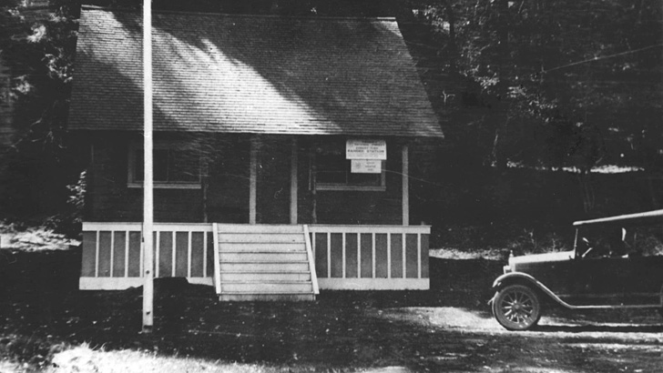 1927. A wooden building with a flagpole and old Model T type of vehicle parked