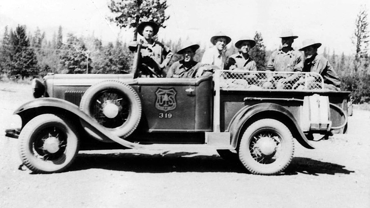 1930. Shows a old pickup with a Forest Service logo and 4 men in the bed and 2 in the seat