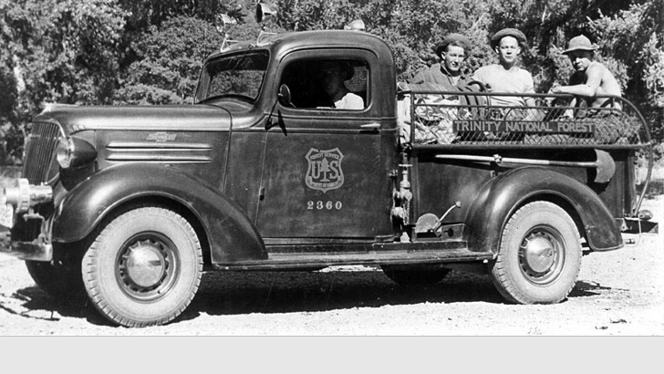 1930s. Shows an old open bed pickup with a driver and three CCC crew members in the back