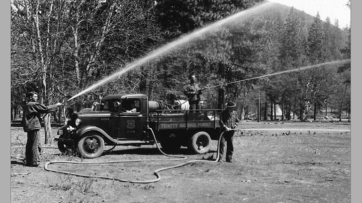 1934. Three CCC members practice with fire hoses from an old style Forest Service fire truck