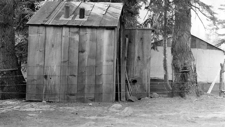 1936. 2 buildings and a tent are visible behind a fence in a forested environment