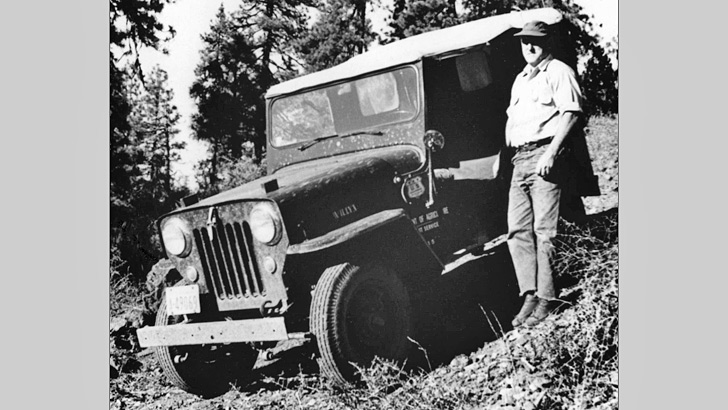 1945. A man stands next to a jeep parked on a sloping, brush covered hill