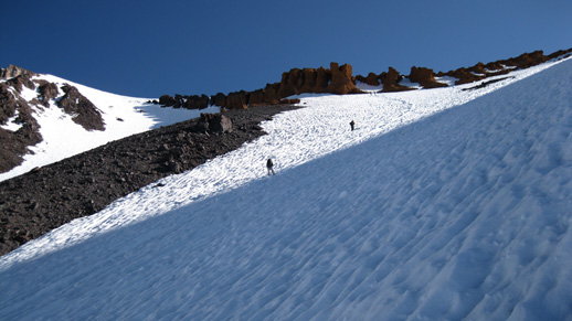 Climbers move up a snow and rock covered landscape
