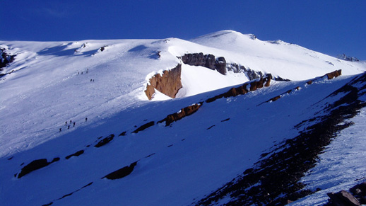 Several climbers are barely visible on a vast, mostly snow covered rocky landscape