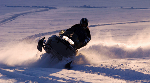 Snowmobile plowing through the snow