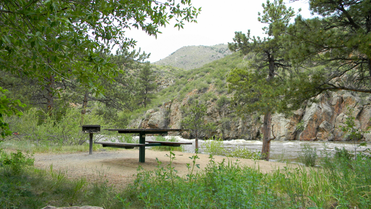 A picnic table and fire grate at the Upper Landing Picnic Site. Cache la Poudre River in background.