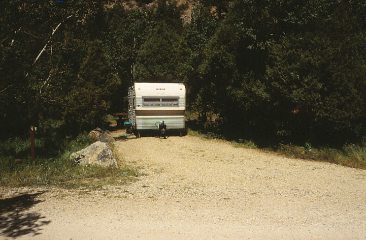 An occupied campsite at number 9 surrounded by trees. A RV with a picnic table in the background.
