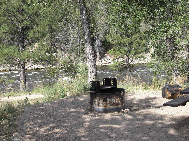 A fire grate with the Cache La Poudre River in the background. Part of the picnic table on the right
