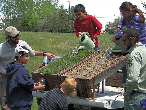 photo of kids pouring water on grass& soil covered culverts