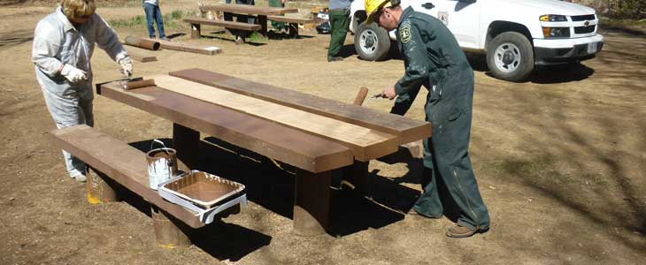 Middle Lion Campground painting new table plank. Crew in background replacing table planks