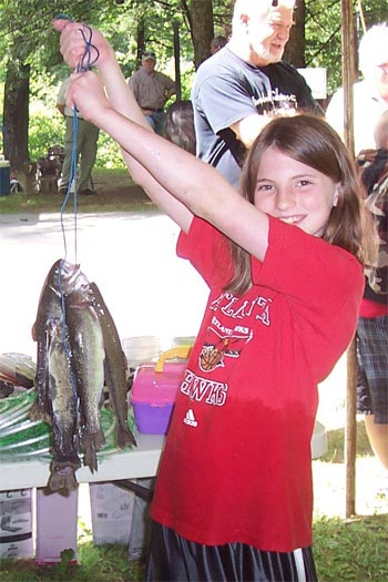 A young angler with a big smile holds up her stringer full of trout.