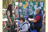 Color photo of Mary Moore, U.S. Forest Service chatting with an Earth Day event participant.