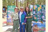 Color photo of Forest Service staff with Earth Day attendee in front of the Forest Service booth.