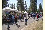 Color photo of the crowd and vendors during the Earth Day event.
