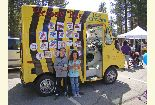 Color photo of two children in front of the Honey Bee ice cream truck during the Earth Day event.